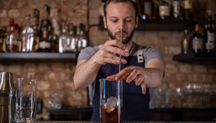 Andrei Marcu mixing a cocktail