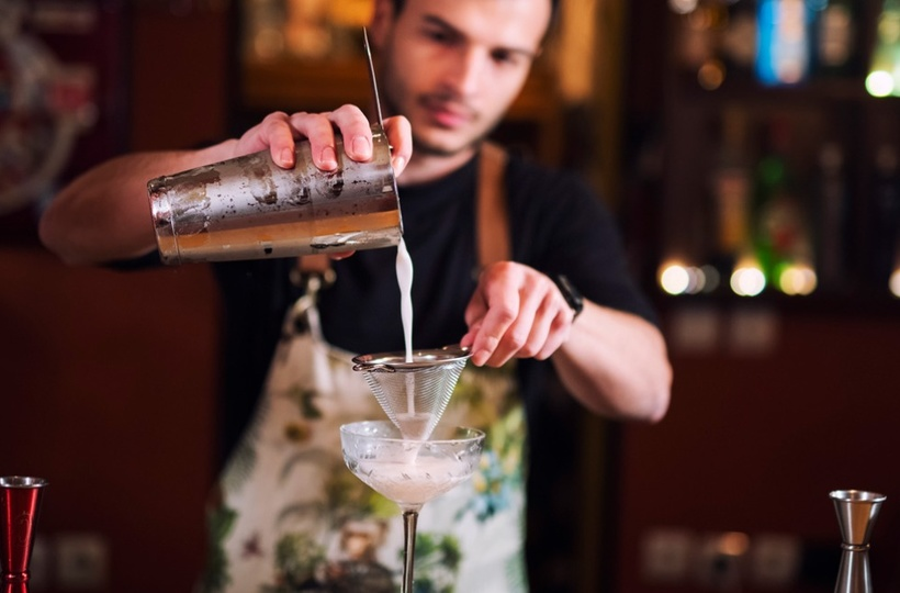 A bartender pouring cocktail in a glass